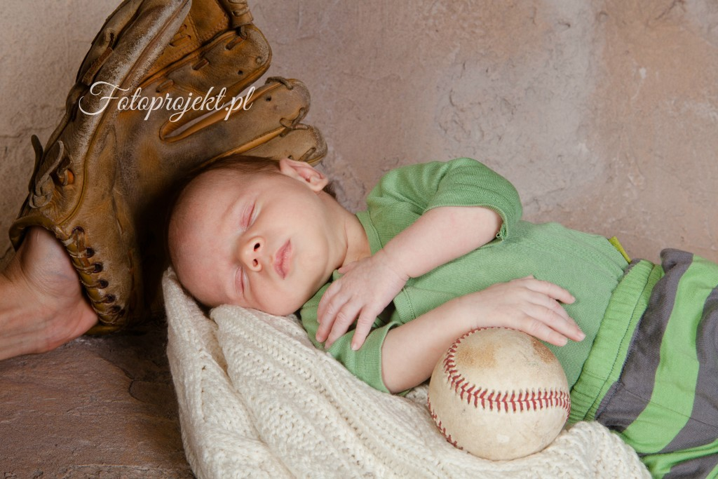 Newborn baby sleeping with baseball and glove